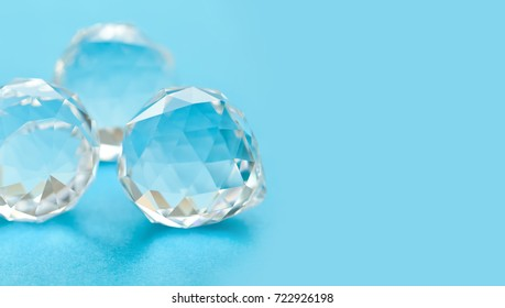 Beautiful crystal gems on blue background. Abstract diamond stones, geometric polygon shapes. Macro view, shallow depth of field, copy space photo