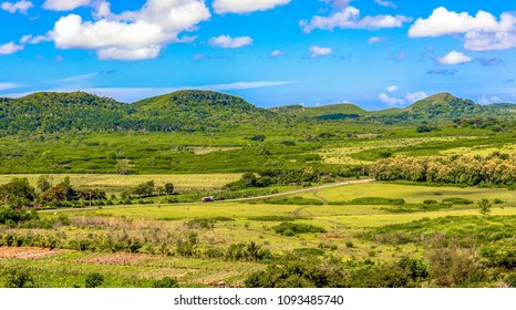 Beautiful Cuban countryside featuring a mountain range. Green farms and a full of clouds sky