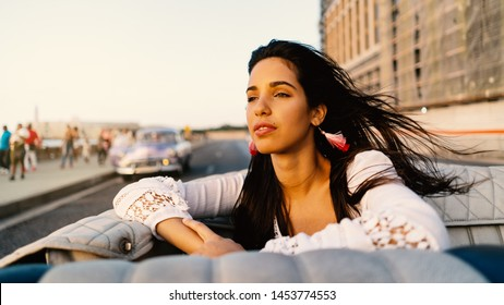 Beautiful Cuban woman portrait on a vintage cabriolet car on the Malecon. Havana, Cuba. Real life style image at sunset.