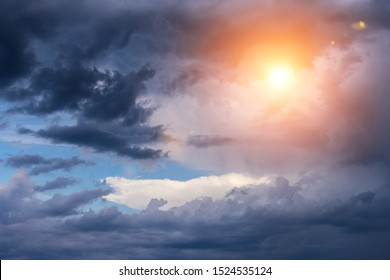 Beautiful cumulus storm dark clouds background with sun and sunlight. Darkness and light