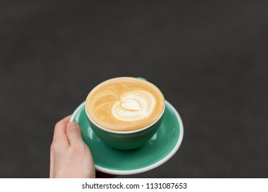Beautiful cup of cappuccino with heart shape latte art holding in hand. Copy space for your text