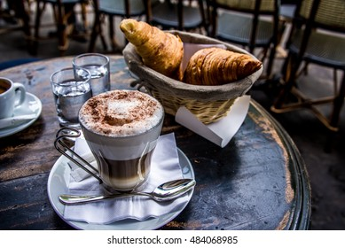 Beautiful cup of coffee cappuccino of latte and two croissant on the  vintage table in cafe, close up, vintage style