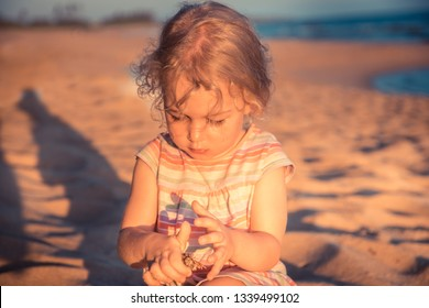 Beautiful curious child girl toddler playing on beach with hermit crab during summer vacation concept childhood lifestyle