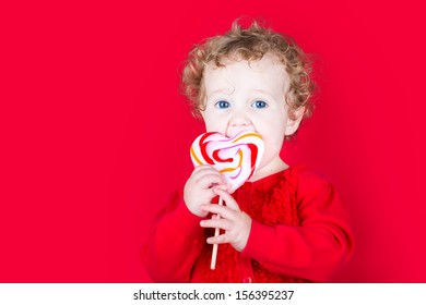 Beautiful curly baby girl eating a heart shaped candy on red background