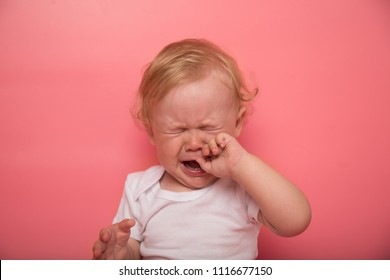 beautiful curly blond baby girl crying on a pink background with finger in mouth. the child has teeth. concept of child care illness. copy space