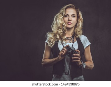 Beautiful curly blonde female photographer dressed in a white t-shirt and waistcoat wears a lot of accessories and wristwatch, posing with a camera at a studio. Isolated on dark textured background.