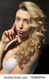 Beautiful curly blonde girl portrait on black background