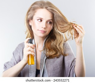 beautiful curly blonde takes care of her hair.Beautiful woman thinking about hair. Dry hair treatment, moisturizing, therapy