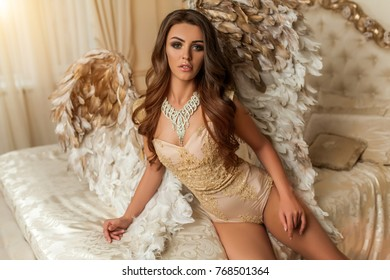 beautiful curly brunette woman with big gold and white wings in the house lies on the bed