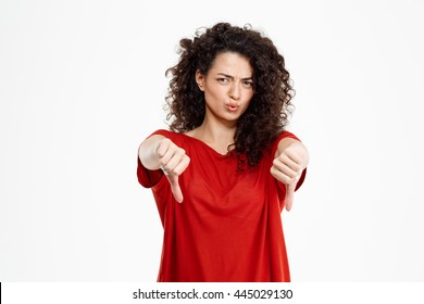 Beautiful curly girl dressed in red t-shirt showing thumb down gesture over white background