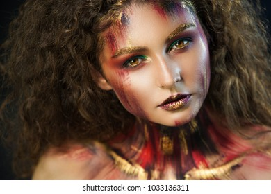 beautiful curly girl in a fire makeup and green shadows under the cloak image created by a make-up artist