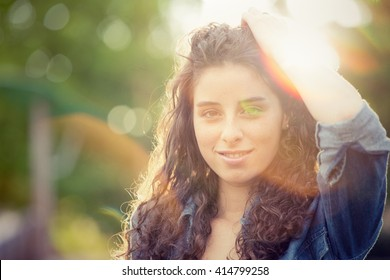 Beautiful curly girl portrait at sunset in a garden