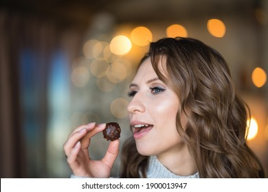 A beautiful curly girl with is trying a vegan chocolate candy with hazelnut.