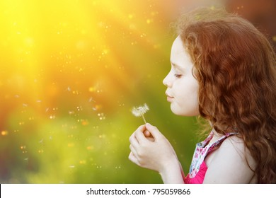 Beautiful curly hair girl blowing dandelion in sunset light. Medical concept.