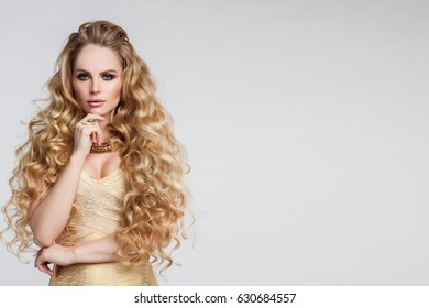Beautiful Curly Hair. With Healthy Wavy Long Blonde Hair. Portrait Happy Woman With Beauty Face, Sexy Makeup And Perfect Hair Curls. Volume, Hairstyle, Hairdressing Concept. High Quality. Jewelry