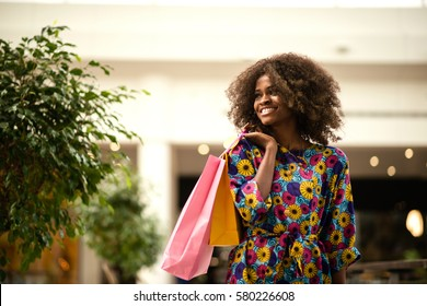Beautiful curly haired afro-american woman standing in a shopping mall with coloured shopping bags in hands.