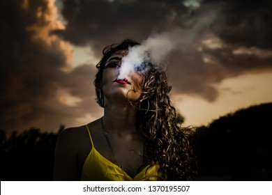 Beautiful, curly haired brunette girl vaping on the beach at dusk with the wind blowing her hair and smoke cloud covering her face. This model has red lips and a yellow dress while smoking her Juul.