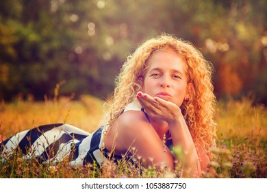 Beautiful curly haired woman throwing a kiss
