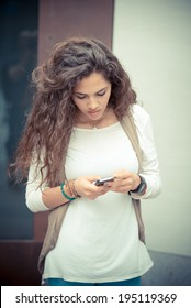 beautiful curly long brunette hair moroccan woman using smart phone in the city
