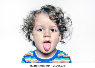 Beautiful curly toddler being naughty, boy with his tongue out