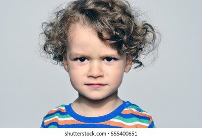 Beautiful curly toddler looking angry, sad boy being naughty