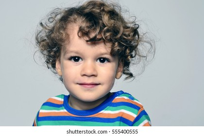 Beautiful curly toddler looking forward, big eyes boy wondering