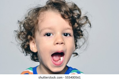 Beautiful curly toddler looking surprised, boy with mouth open showing his white teeth