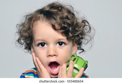 Beautiful curly toddler looking surprised, boy with mouth open holding a car toy in his hand