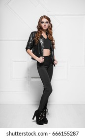 Beautiful curly woman dressed in black leggings and leather jacket posing near the wall