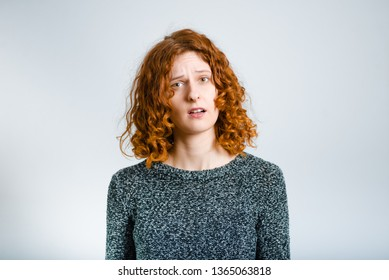 beautiful curly woman is indignant, isolated on gray background