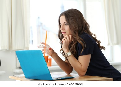 Beautiful, curly woman with laptop
