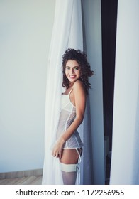 Beautiful curly woman in white lingerie, smiling