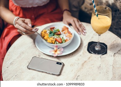 Beautiful curly-haired brunette girl eating breakfast in a smoothie cafe, using smartphone, healthy breakfast smoothie bowl and a drink made of super foods, fruits, nuts, berries, granola