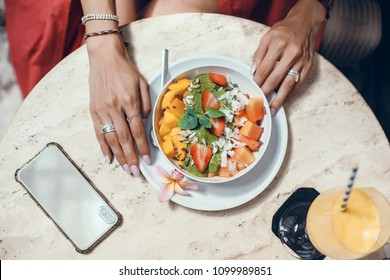 Beautiful curly-haired brunette girl eating breakfast in a smoothie cafe, using smartphone, Woman's Hands Holding a Pink Fruit Smoothie Bowl Topped with Frozen Berries and a Watermelon Star juice,yoga