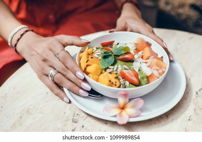 Beautiful curly-haired brunette girl eating breakfast in a smoothie cafe, using smartphone, Young girl having a good morning healthy breakfast smoothie bowl and a drink made of super foods, fruits,