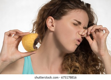A beautiful curly-haired girl holds a foul banana, lemon and mandarin in her hands and holds onto her nose and frowns at the stench