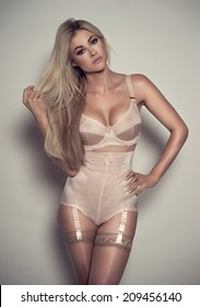 Beautiful curvaceous, busty tanned blond woman in lingerie wearing a sexy corset, suspenders, stockings and bra standing looking at the camera with a sultry seductive expression