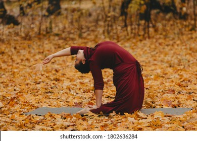 Beautiful curvy girl doing yoga in nature on a autumn day. Body positive, sports for women, harmony, asana, healthy lifestyle, inspiring look, self-love and wellness.