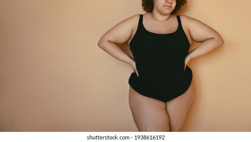 Beautiful curvy oversize African black woman afro hair posing in black bodysuit on beige brown background isolated, body imperfection, body acceptance, body positive and diversity concept. Copyspace