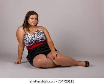 Beautiful Curvy Teenage Girl Wearing Pretty Black and White Striped Dress Laying on Gray Background