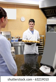 Beautiful customer waiting for bread in a cafeteria and smiling at the baker