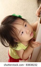 Beautiful and cute Asian 14-month old baby toddler girl playing with door latch and looking up