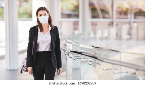 Beautiful cute Asian businesswoman wearing protective surgical hygiene mask on face in the situation of coronavirus outbreak, walking to office in city. Idea for preventing, protect health from virus.