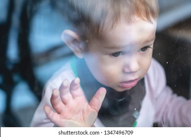 Beautiful cute baby boy looking in the window glass with reflection. Concept of loneliness of children and waiting for kindness. Orphanage and orphans