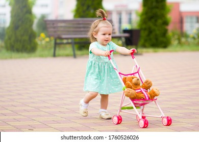 Beautiful cute baby child plays with baby stroller caring positive association care. Walk rest in the park with mom happy childhood with your favorite toy bear.