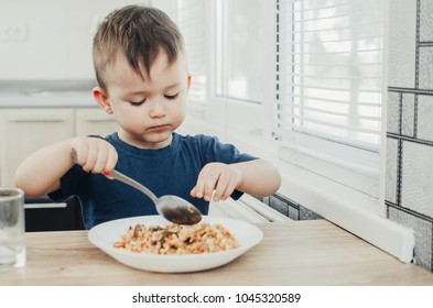 beautiful cute baby eats rice with a spoon in the kitchen, very fun