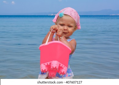 Beautiful cute baby girl in swimsuit playing on the beach