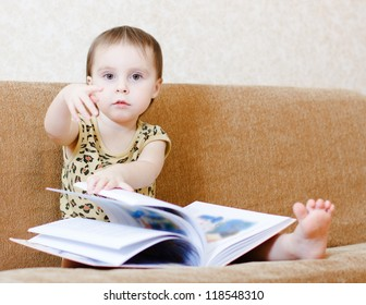 Beautiful cute baby reading a book while sitting on the couch.