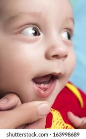 Beautiful cute baby shows the calf's teeth
