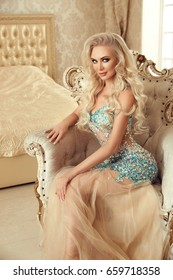 Beautiful cute blond bride woman with long wavy hair in luxurious dress posing on modern armchair in luxury bedroom. Fashion indoor portrait.